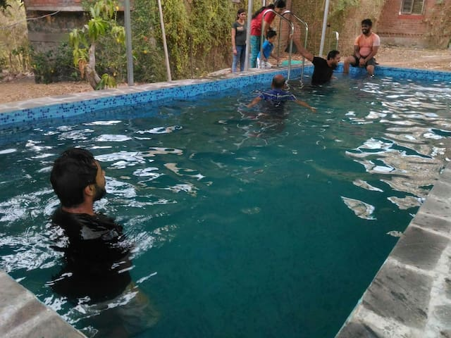 Swimming pool at farmhouse near Mumbai for groups.