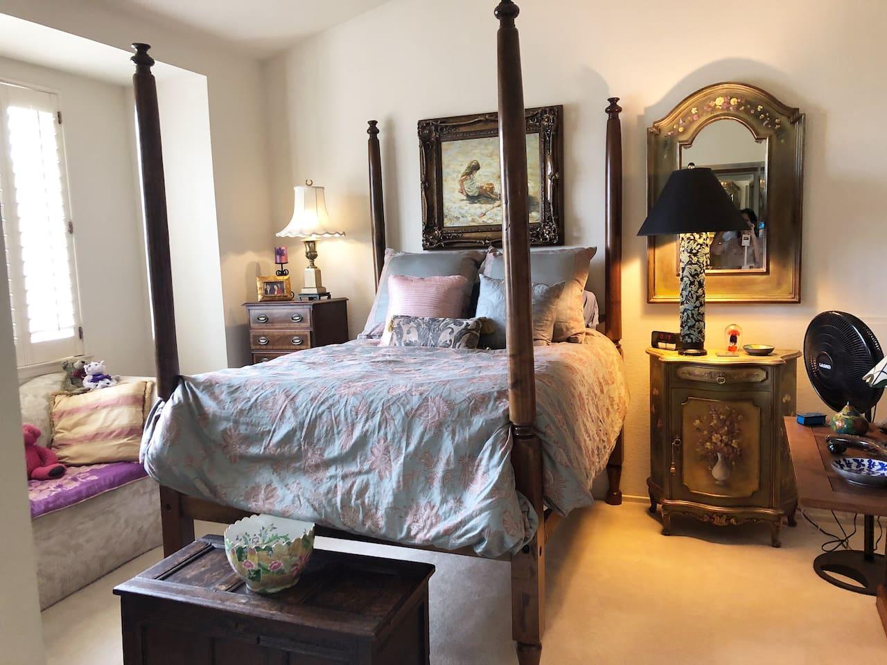 Bedroom with lots of light, desk, fan, closets.