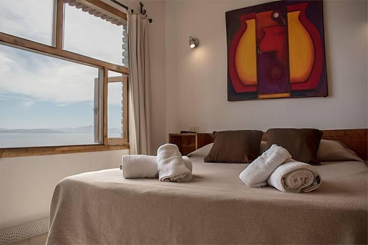 Habitación con cama matrimonial , TV  y vista al lago.