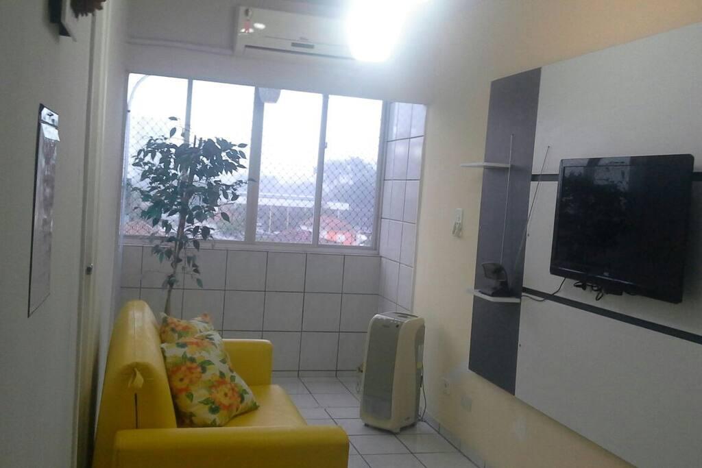 Sala climatizada com tv e sofá cama