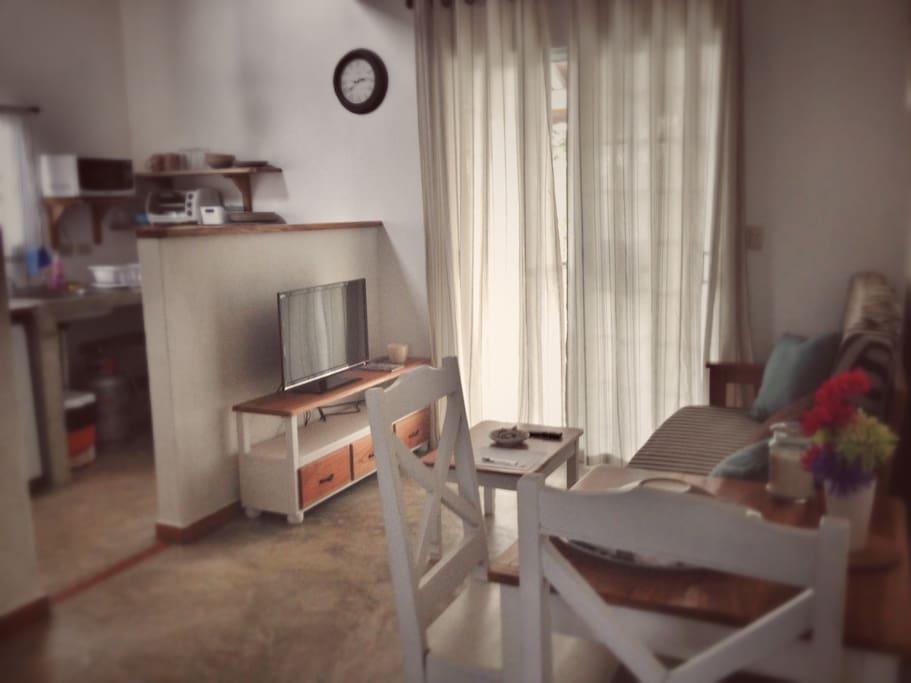 Sala de estar con TV y mesa de comedor, cocina al fondo