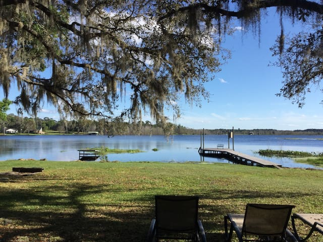 Beautiful lakefront yard with dock and concrete boat ramp on premises.