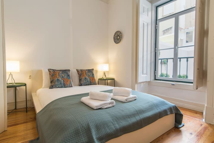 A very comfortable queen-sized bed with a large window that lets in plenty of natural light throughout the day