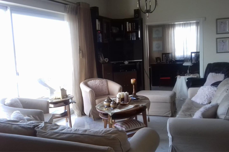 σαλόνι στον πρώτο όροφο με τριθέσιο, διθέσιο καναπέ και τρεις πολυθρόνες.  Τα μεγάλα παράθυρα προσφέρουν πανοραμική θέα των Μεγάρων