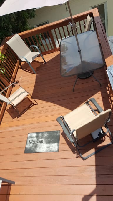 Wood Deck w/ Patio Table, Chairs, & Umbrella.