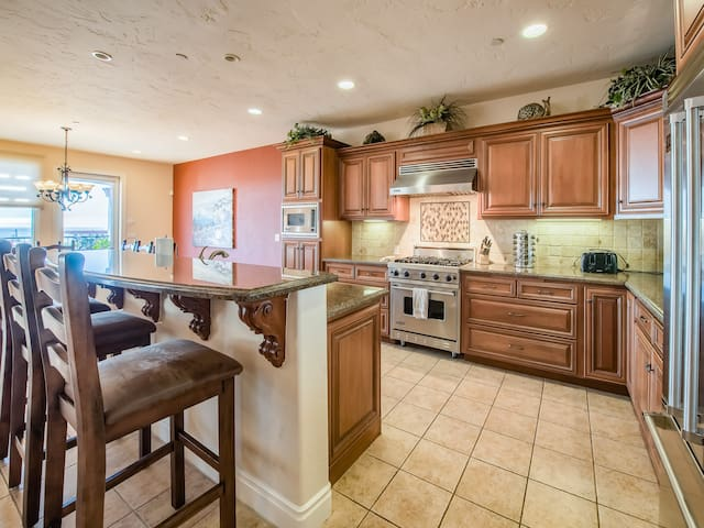 The gourmet kitchen features granite counters and a travertine backsplash.