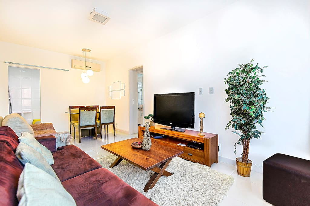 Large, modern, spacious living room area with open dining room, Plasma TV, Split Air-conditioning unit, tan sofa is folds out into sofa bed.