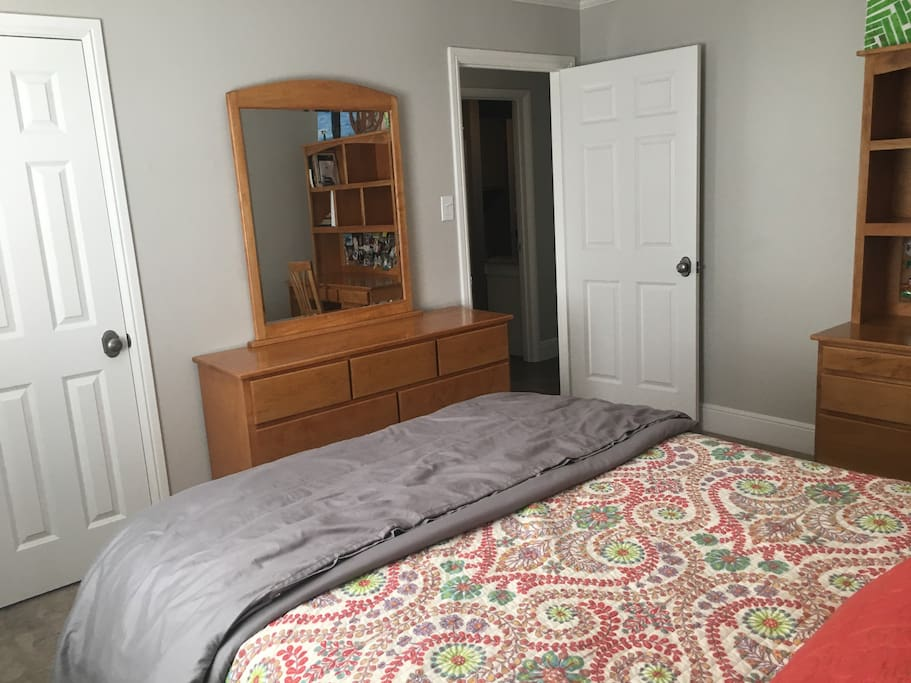 Queen bed with closet, dresser, and desk.