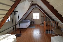 Comfortable upstairs bedroom with three beds.