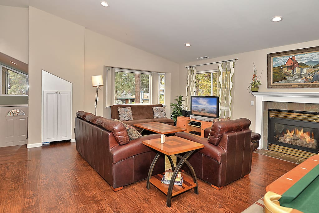 Gas fireplace, flat screen TV, and leather seating gathered around both.