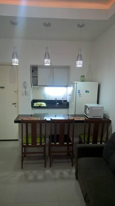 Vista da sala integrada a cozinha tipo americana, totalmente equipada.