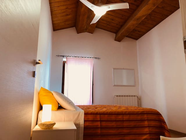 Camera matrimoniale Happy, luminosa, armadio e due comodini bianchi dotati di abat-jour ad intensità luminosa, soffitto con travi in legno, ventilatore a lampadario nel colmo.