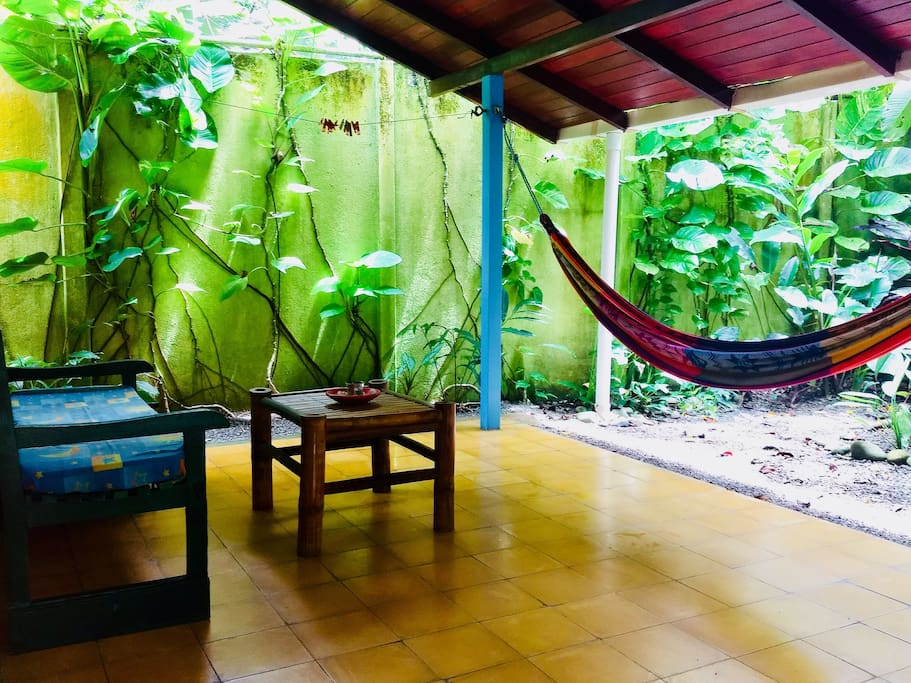 Porch with two hammocks (one not pictured), seating area and coffee table, facing a tropical garden.