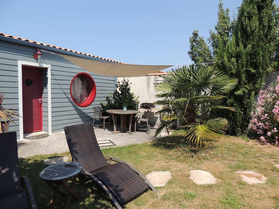 Vue du jardin avec terrasse table et plancha et transat