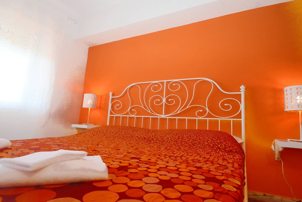 Wide orange double room with 1 double bed and 1 bunk bed