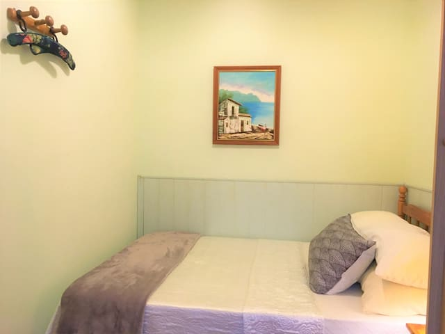 The bedroom has a double bed, pillows, blankets; bedside tables and a wardrobe with hangers for clothing;