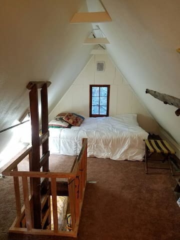 The loft bedroom with queen size bed and window looking out to the forest and creek