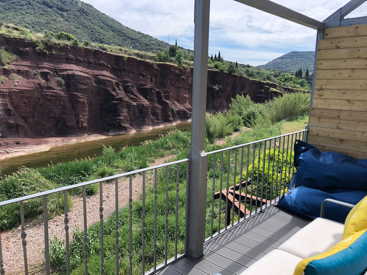 Terrasse plein sud avec canapé pour 2 personnes, fauteuil et pouf. Vue sur les falaises rouges du Salagou. Rivière privative.