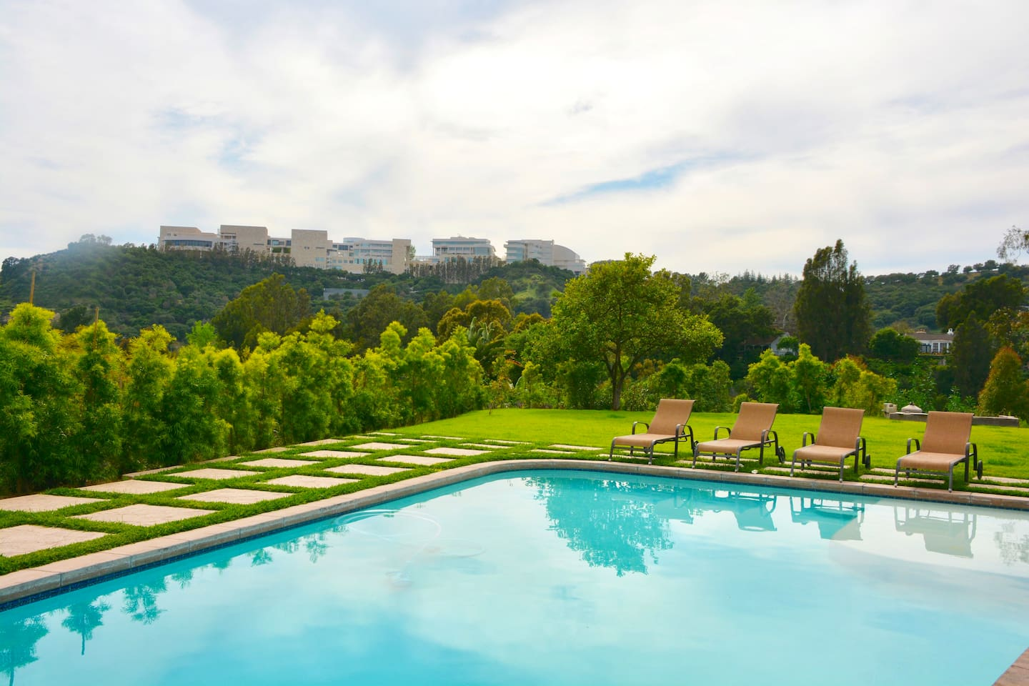 Patio view of the pool, mountains, and Getty Museum