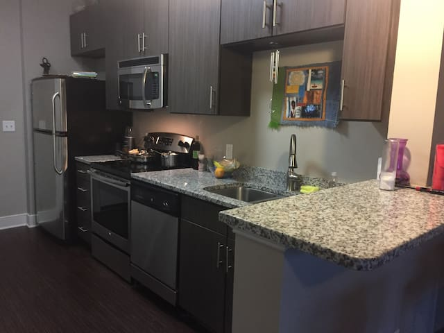 kitchen with granite countertops, stainless steel appliances, dishwasher, microwave, ice maker, garbage disposal and vinyl/wood flooring