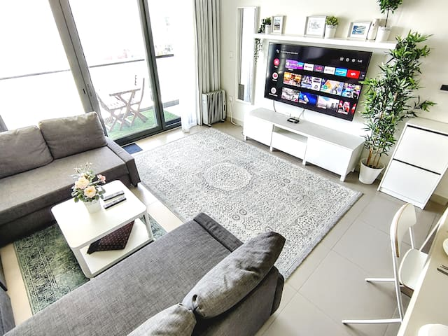 """Sitting area with balcony, 65"""" Sony Smart TV, and two queen-sized sofa beds"""