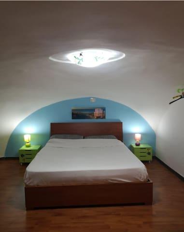 Ampia camera da letto con comodini , comò, appendiabiti e ventilatore.