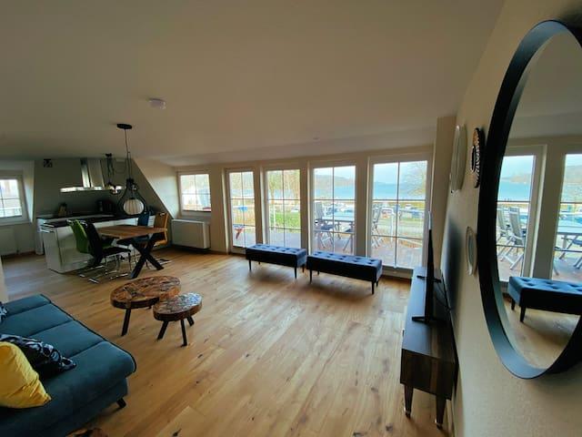 Das großzügige Wohnzimmer bietet durch die große Fensterfront einen wundervollen Ausblick auf die Flensburger Förde