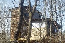 "The south facing area of the Choctaw Treehouse... the two story on the left is all bedrooms... The common room on the right has two separate twin bunks and a bathroom.  The bathroom has a modern flush toilet, wash basin and an over-sized shower for handicap... All door are 36"" wide."