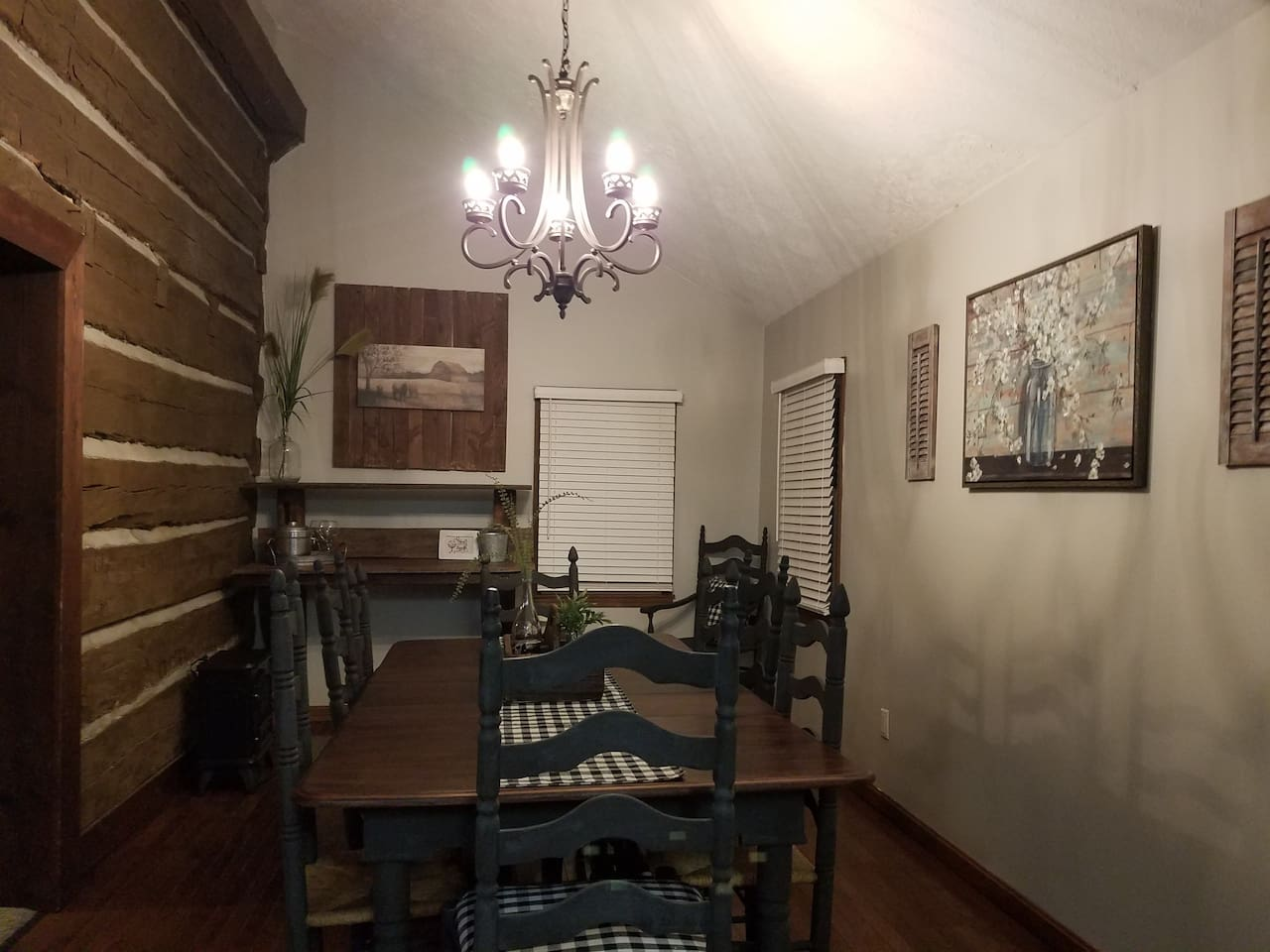 Dining room with seating for 8-10 and exposed log wall.