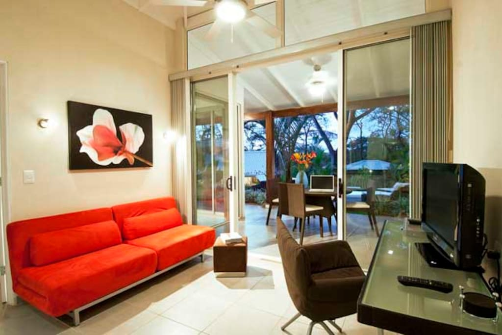 Bright living room w/ pullout couch, dining patio
