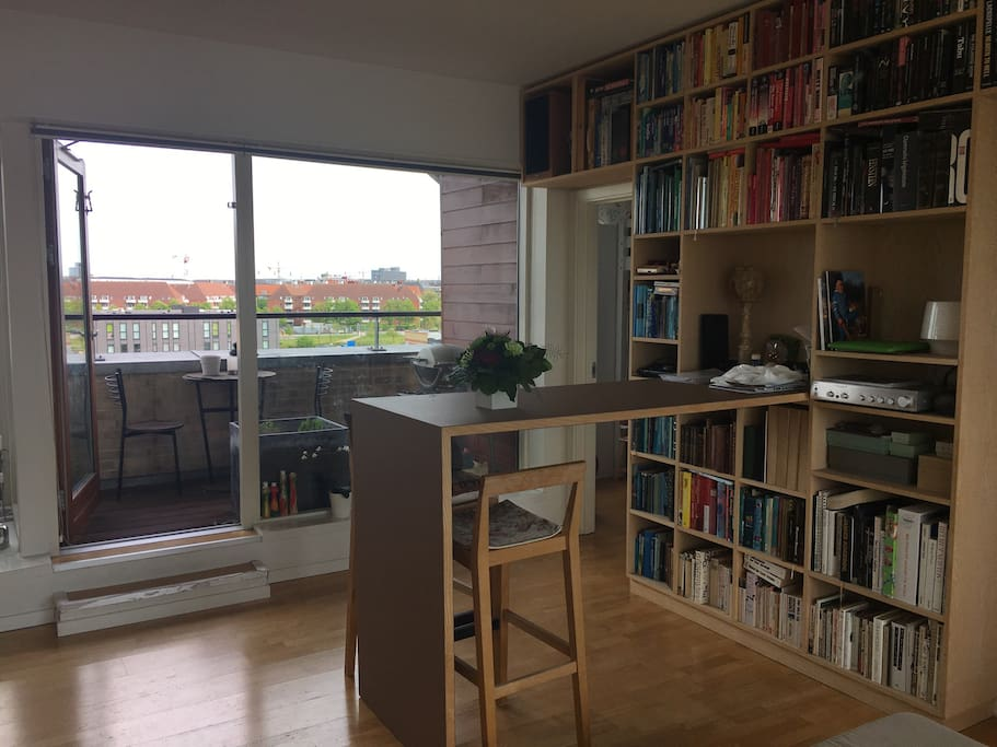 Livingroom with door to balcony and view over Nørrebro and sunrise
