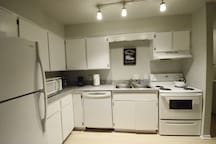 Kitchen with granite counter, oven, microwave, dishwasher, and full size fridge