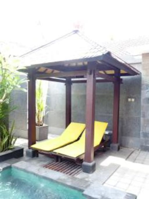 Bali hut and deck chairs looking over pool