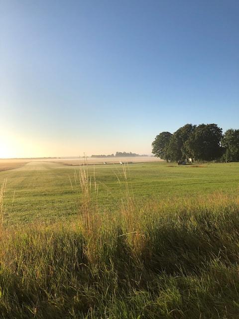Hus med udsigt over marker og strand