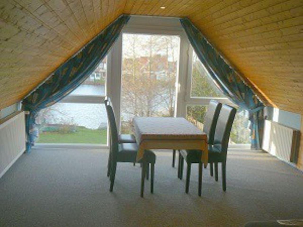 Essplatz im Wohnzimmer mit Panoramafenster und Blick auf den See
