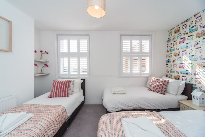 We love the funky VW camper van wallpaper in here. This room can be three singles or a double and single. There are direct distant seaviews from the windows