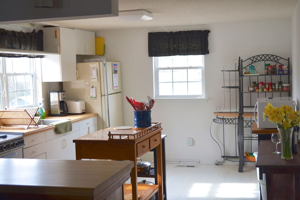 Kitchen with microwave, coffee maker, toaster, gas oven, refrigerator, & blender