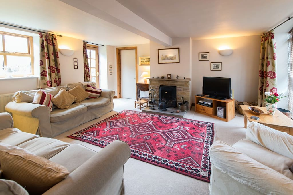 Lounge with attractive arched window, open fire and views over the garden to open countryside.