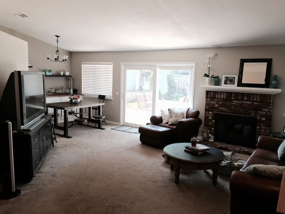 Large , open, comfy living room with cable television .