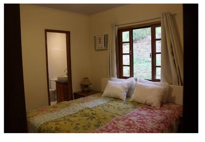 Suite com cama Queen e colchão de molas, ar condicionado e roupas de cama e banho de 100% algodão.