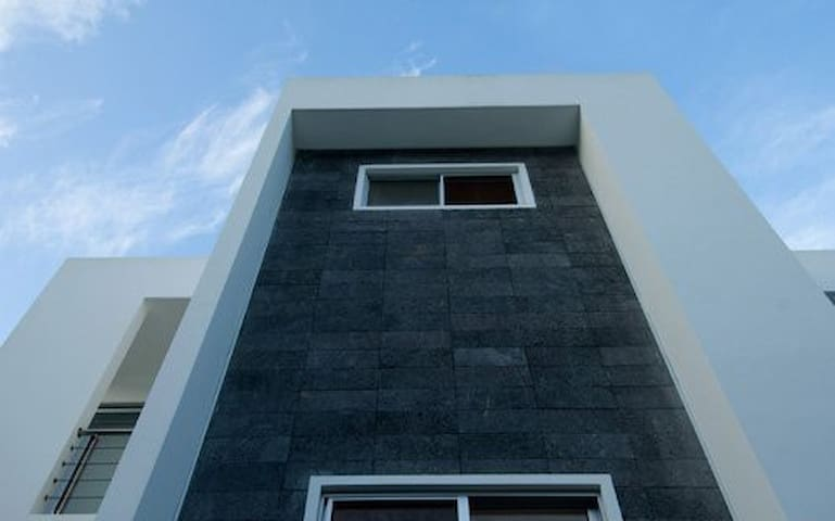 Structural white concrete and raw granite are among the house's building materials.