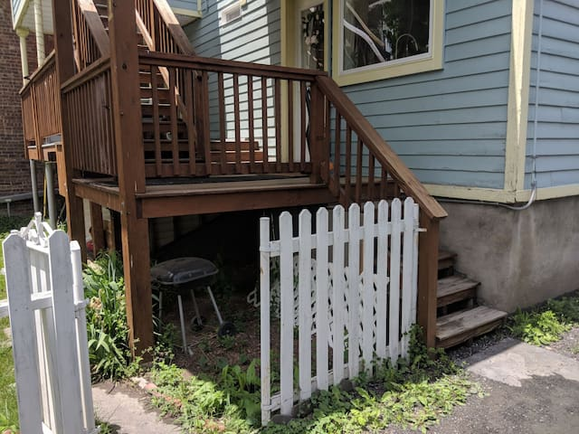 Gate into small back yard with table and 4 chairs (shared area with downstairs rental) and the back stairs to both apartments private entrances.
