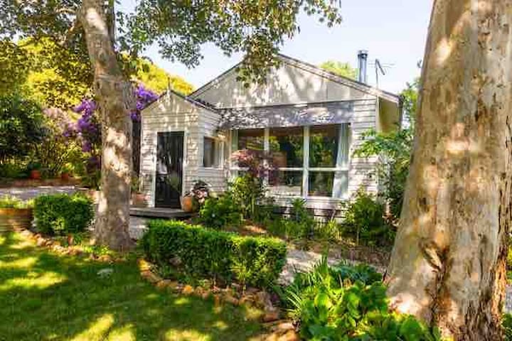 Nandi Cottage in positioned in a beautiful garden setting, surrounded by trees, with garden views from every window