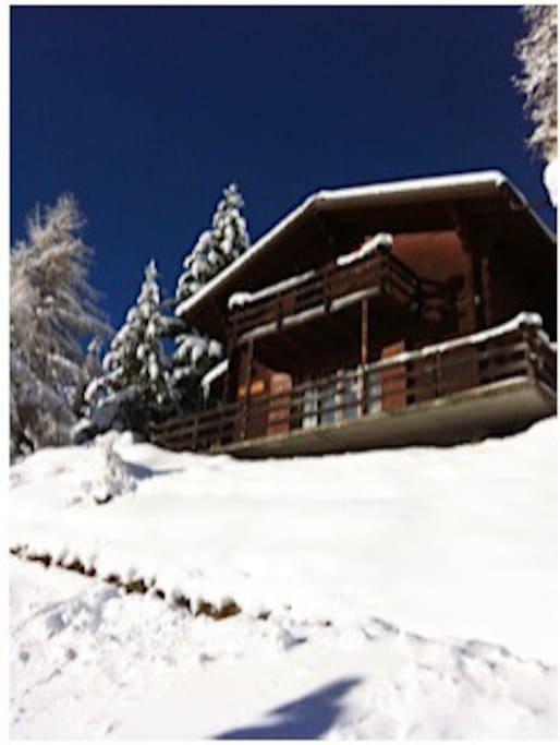 Le chalet sous la neige avec le ciel pur de l'hiver