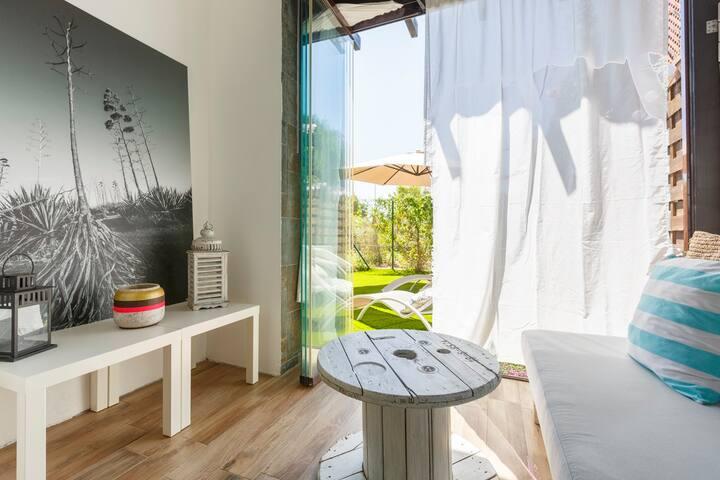 """Zona Chillout, aprovechando una antigua bobina de cables para hacer una mesita , junto a una fotografía en gran formato de las """"pitas"""" del Cabo de Gata . Un sofá reciclado de palets donde echar una buena siesta mientras la brisa mece las cortinas"""