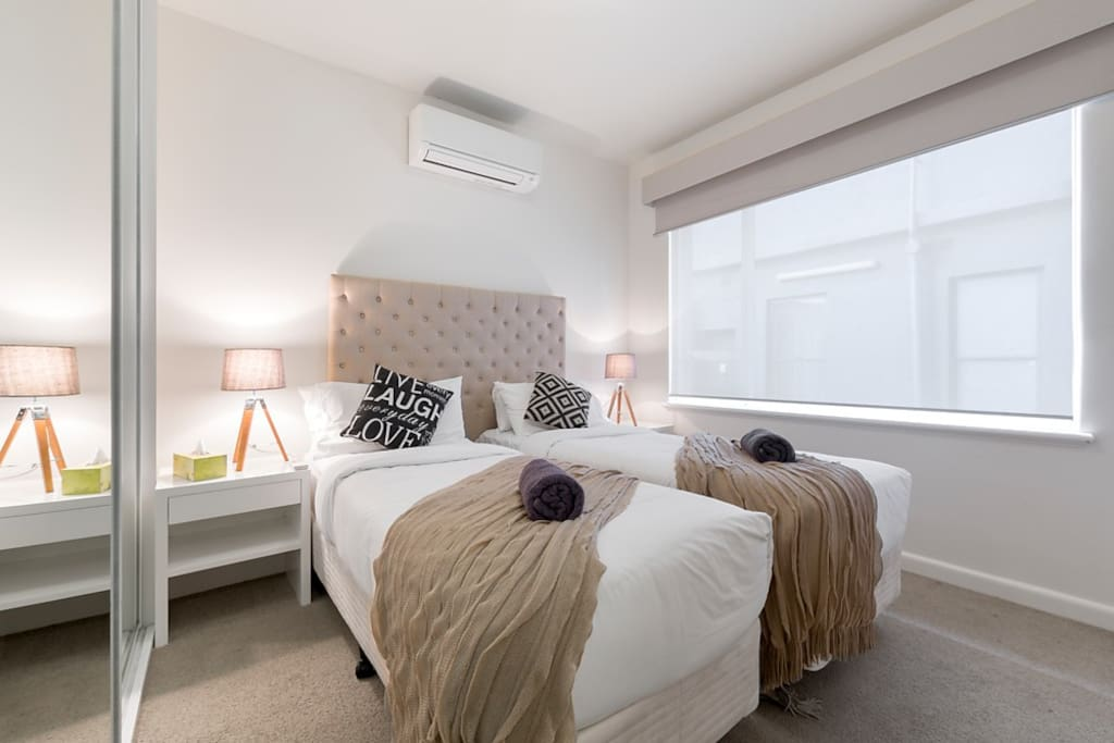 Splittable queen bed with air con, large mirrored robes and double glazing, in this StayCentral 2 bedroom serviced Brunswick apartment