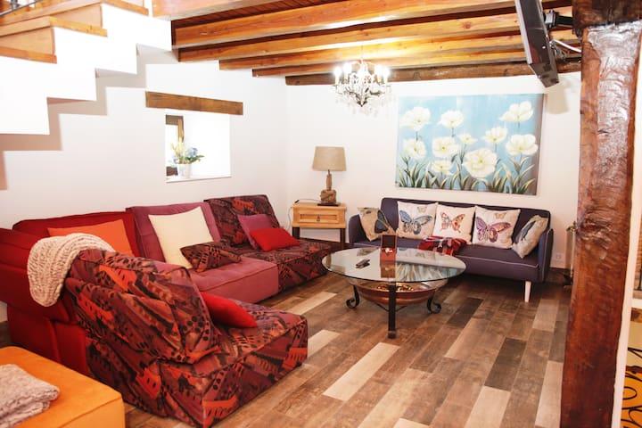 Petraenea Casa Rural, salón con televisor, sofá personalizado. rincones con encanto. espacios para reunirse.