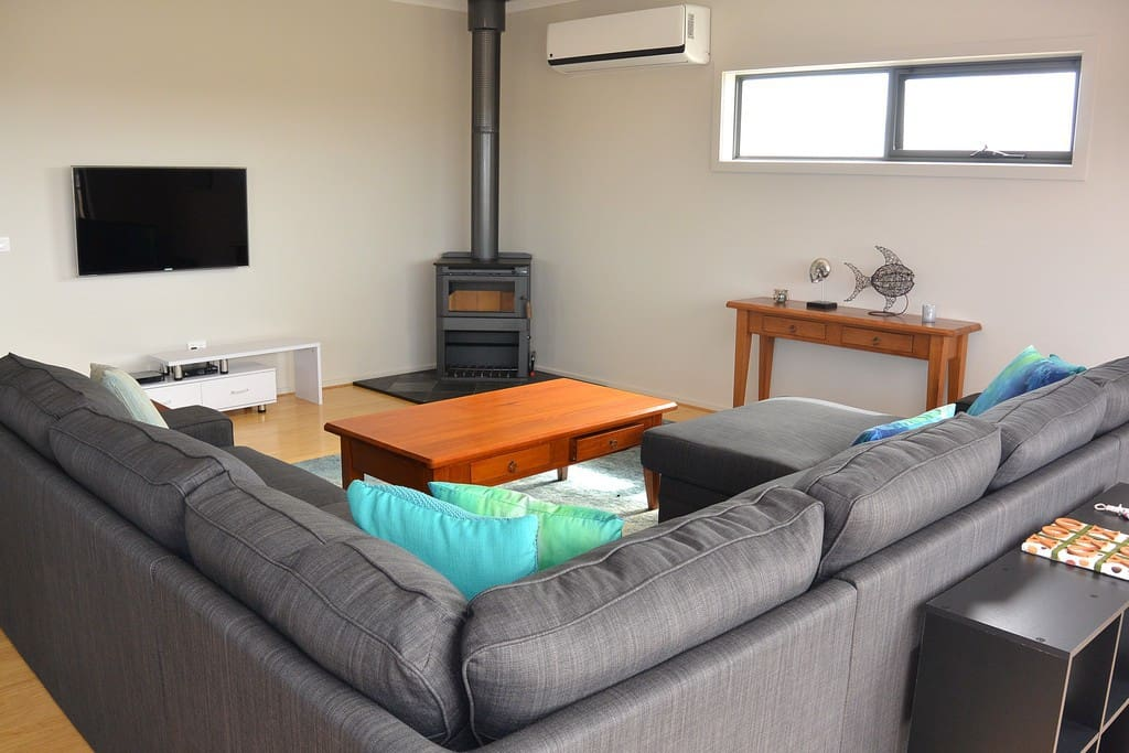 Super comfy lounge with wood heater, wall mounted TV and DVD