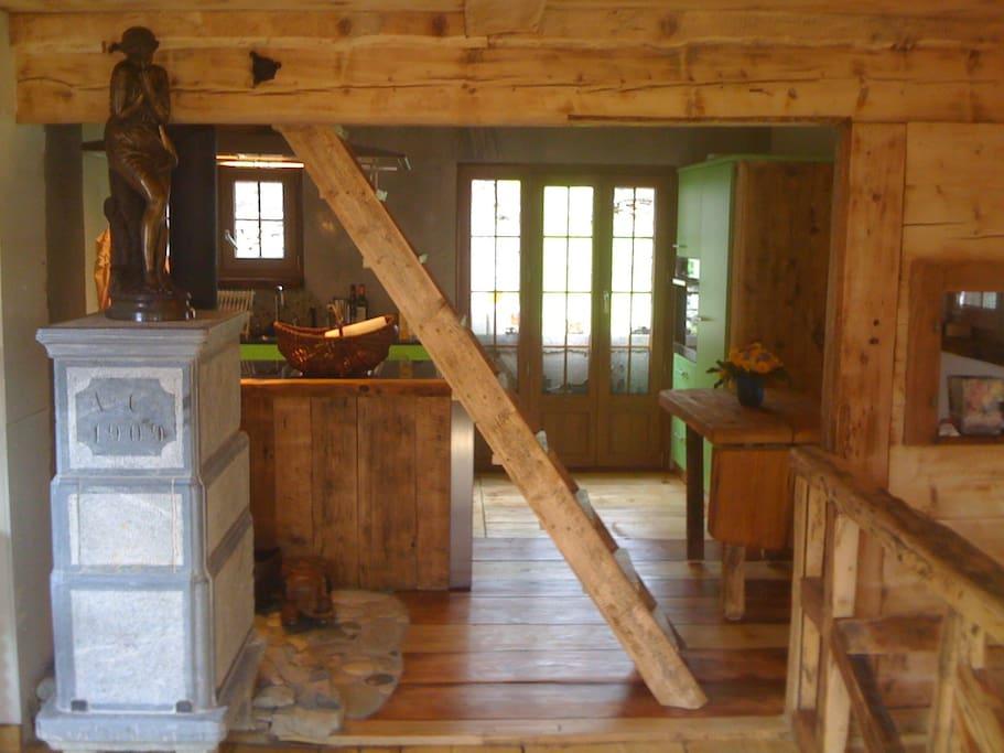 La cuisine depuis le salon avec l'escaliers qui monte à la mezzanine, 3 lits.
