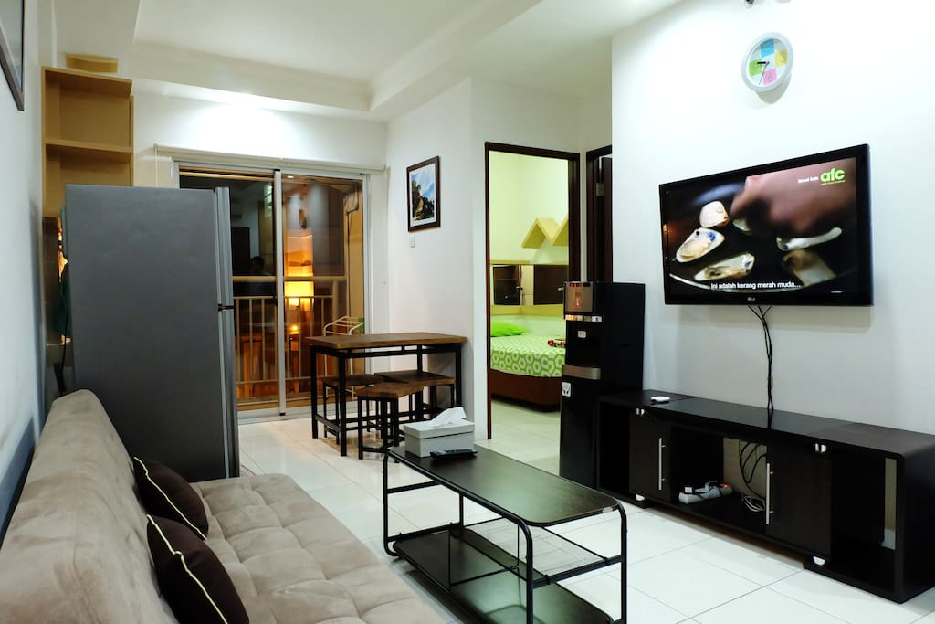 Spacious Living Room With TV, Referigerator and Water Dispenser